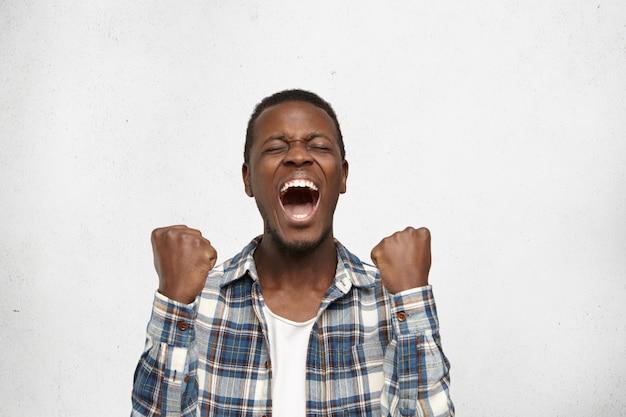 Emotionele succesvolle gelukkige afro-amerikaanse man die schreeuwt met wijd open mond en gesloten ogen, balde zijn vuisten terwijl hij juicht nadat hij onverwacht in de loterij heeft gewonnen. menselijke emoties en gevoelens