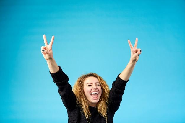 Emotionele tevreden jonge aantrekkelijke gember krullende vrouw met geopende mond die en een succes viert dat handen opheft met het teken van overwinning op blauwe achtergrond opheft.