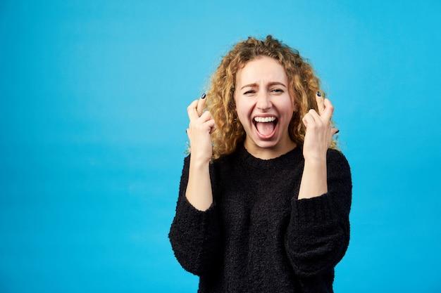 Emotionele tevreden jonge aantrekkelijke roodharige krullende vrouw met geopende mond die vingers kruist voor geluk.