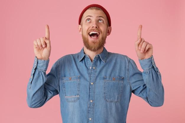 Emotionele tevreden jonge bebaarde man kijkt op met opwinding en brede glimlach, houdt de handen omhoog en wijst met de voorste vingers naar boven, gekleed in een spijkerblouse, geïsoleerd