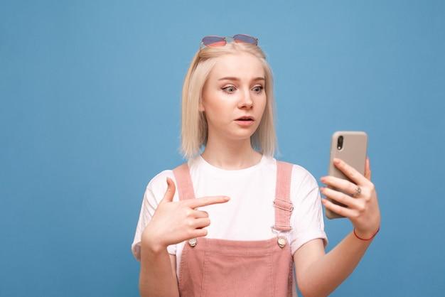 Emotionele tiener meisje in schattige kleding maakt gebruik van een smartphone met een verbaasd gezicht op een blauwe achtergrond