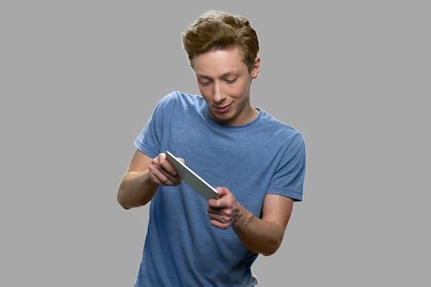 Emotionele tienerjongen die mobiel spel speelt. expressieve tiener man met smartphone. verslavingconcept voor mobiele telefoons en sociale media.
