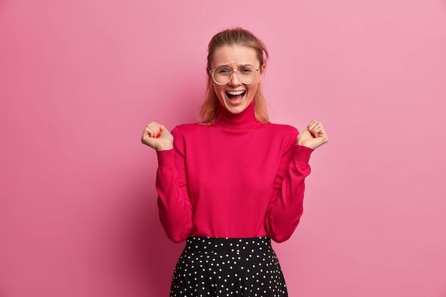 Emotionele tienermeisje roept luid haar handen op, houdt de mond open, reageert op iets geweldigs