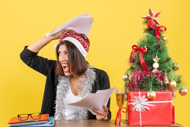 Emotionele uitgeput zakelijke dame in pak met kerstman hoed en nieuwjaarsversieringen met documenten en zittend aan een tafel met een kerstboom erop in het kantoor