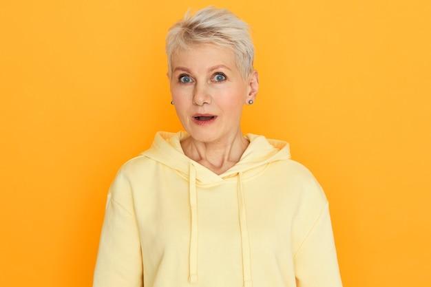 Emotionele verbaasde vrouw van middelbare leeftijd met geverfd pixiekapsel die mond opent en naar de camera staart in vol ongeloof, geschokt is door verkoopprijzen, online winkelt, poseren geïsoleerd tegen gele muur
