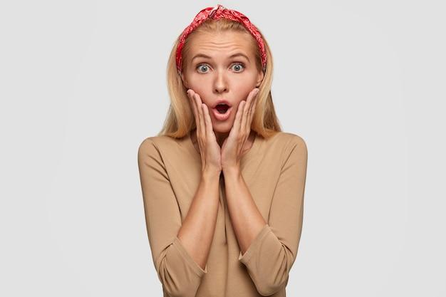 Emotionele verrast blonde vrouw raakt wangen met handpalmen, draagt rode hoofdband en beige trui
