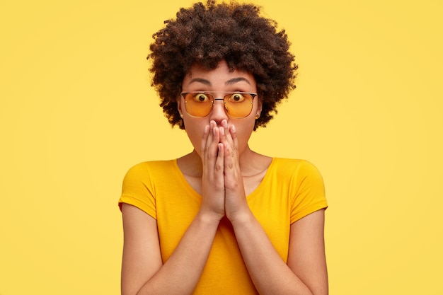 Emotionele verrast donkere vrouw met een verbijsterde uitdrukking, heeft betrekking op mond met beide handen