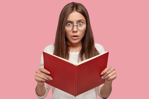Emotionele verrast jonge vrouw draagt een ronde bril