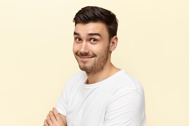 Emotionele verrast jongeman met borstelharen die wenkbrauwen optrekken met een verbaasde gezichtsuitdrukking onder de indruk van intrigerend nieuws