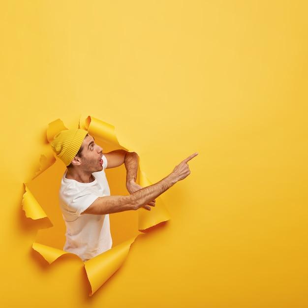 Emotionele verrast man staat in papiergat met gescheurde gele randen, toont ongelooflijke kopie ruimte