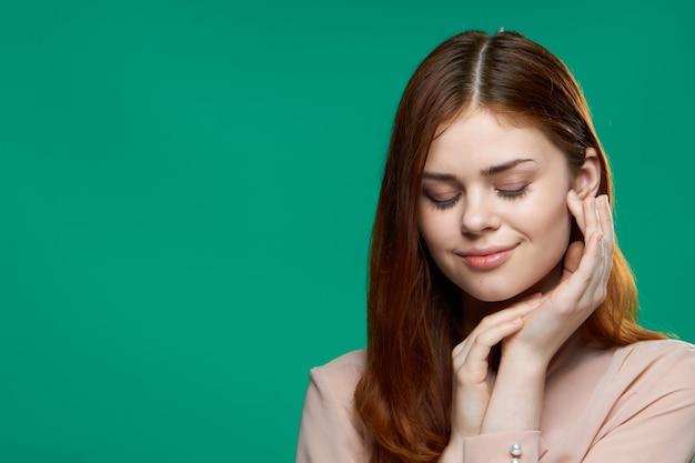Emotionele verrast vrouw hand in hand in de buurt van gezicht studio levensstijl groene achtergrond