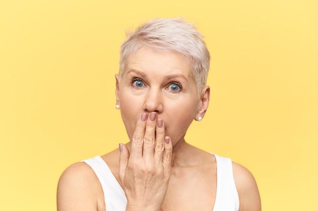 Emotionele volwassen vrouw met bug-eyed met kort haar die volledig ongeloof uitdrukt, mond bedekt met hand, intrigerend geheim, onverwacht nieuws of roddels afluistert.