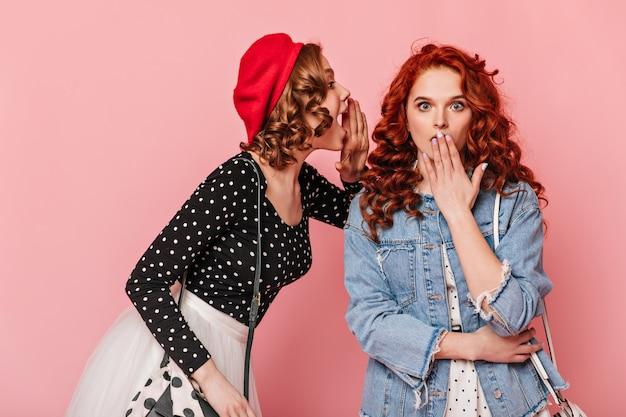 Emotionele vrienden praten op roze achtergrond. franse dame die roddels deelt met zus.
