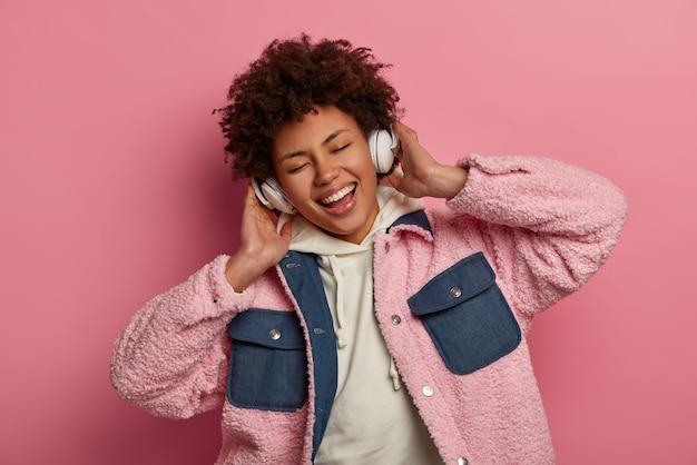 Emotionele vrolijke afro-amerikaanse vrouw luistert naar muziek van favoriete band