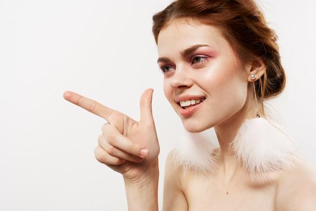 Emotionele vrouw blote schouders pluizige oorbellen luxe heldere huid lichte achtergrond. hoge kwaliteit foto