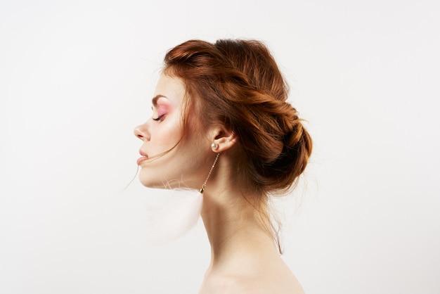 Emotionele vrouw blote schouders pluizige oorbellen luxe heldere huid lichte muur.