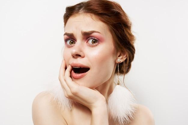 Emotionele vrouw blote schouders pluizige oorbellen luxe heldere huid lichte ruimte