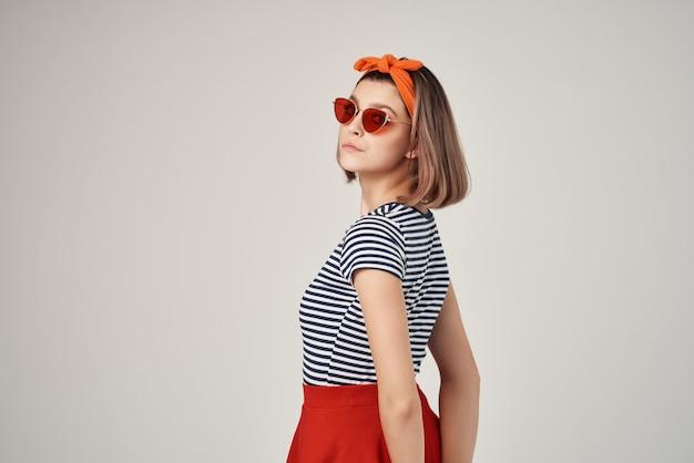 Emotionele vrouw die een zonnebril draagt in een gestreepte t-shirt die poseert