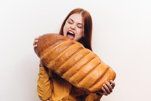 Emotionele vrouw die haar mond wijd opent honger brood van meel product