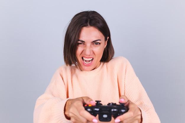 Emotionele vrouw die spelletjes speelt met joystick op grijze muur
