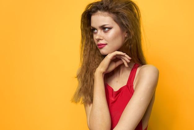 Emotionele vrouw golvend haar lichte make-up levensstijl gele achtergrond