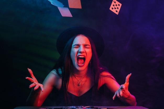 Emotionele vrouw gooit kaarten over aan een pokertafel in een casino. concept van winnen en verliezen bij gokken