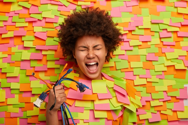 Emotionele vrouw heeft hulp nodig van professionele technicus, houdt veel kleurrijke kabels vast, weet niet hoe ze alle snoeren op de computer moet aansluiten, steekt haar hoofd uit, omringd met veel stickers, heeft mond open