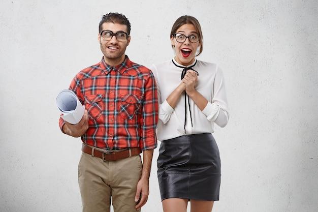 Emotionele vrouw houdt handen bij elkaar, staart met verbazing naar camera staat naast mannelijke collega die blauwdruk houdt