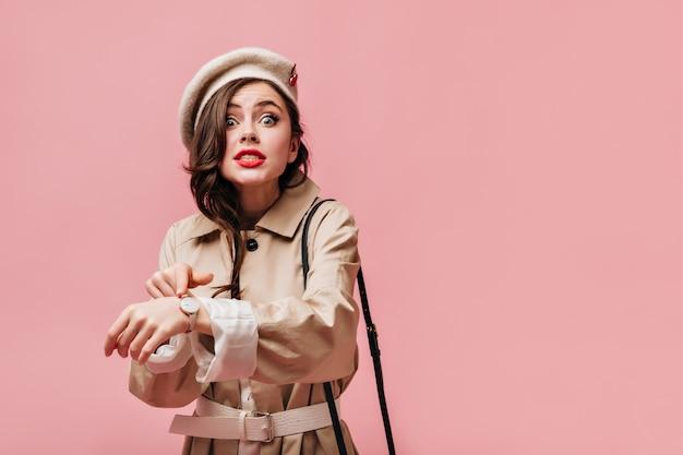 Emotionele vrouw in beige trenchcoat en lichtgekleurde hoed kijkt naar de camera en wijst naar polshorloge.