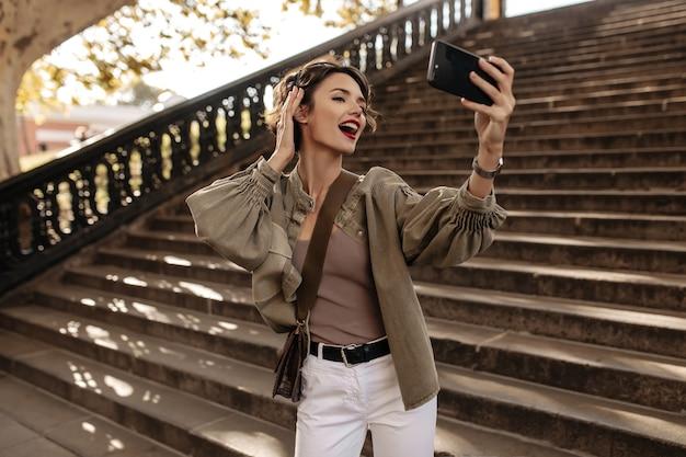 Emotionele vrouw in denim jasje en witte spijkerbroek selfie maken. krullende vrouw die met handtas buiten foto neemt.