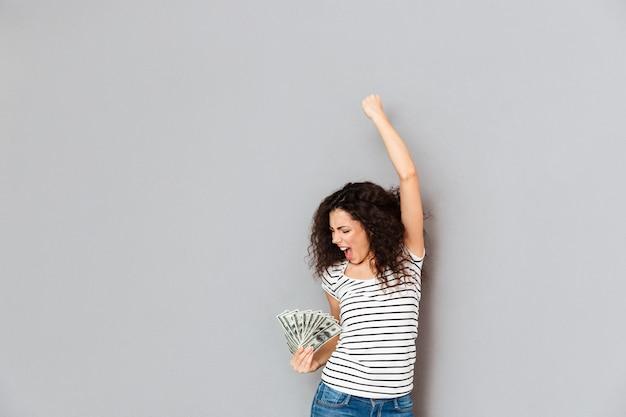 Emotionele vrouw in gestreept t-shirt gedraagt zich als winnaar van fan van 100 dollarbiljetten en balde vuist in de lucht over grijze muur