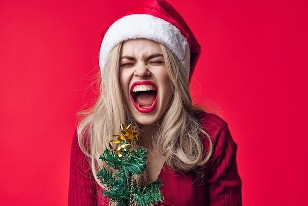 Emotionele vrouw in santa kostuum mode kerstboom met vakantie speelgoed