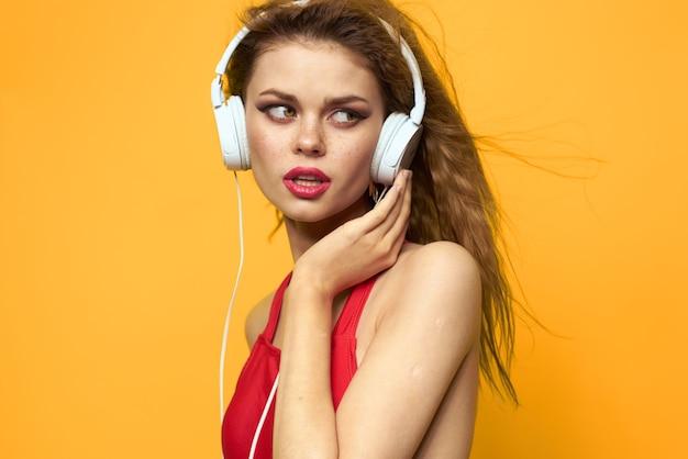 Emotionele vrouw in witte koptelefoon luistert naar muziek leuke levensstijl gele achtergrond