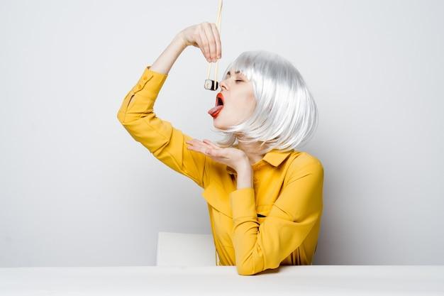 Emotionele vrouw in witte pruik zit aan de tafel met sushibroodjes
