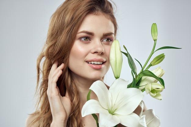 Emotionele vrouw met bloemen lente model naakte schouders heldere huid