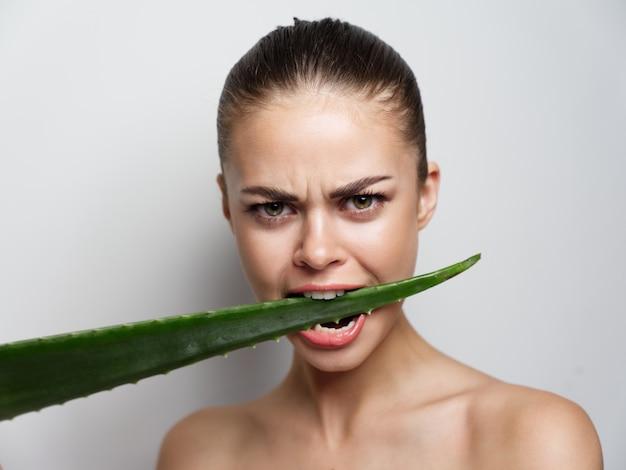 Emotionele vrouw met blote schouders knaagt aan een groen blad op een licht kapselmodel als achtergrond