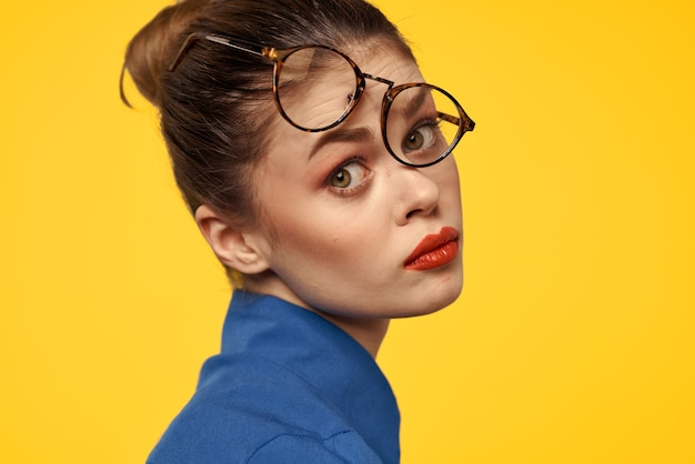 Emotionele vrouw met bril op haar gezicht grimassen op geel
