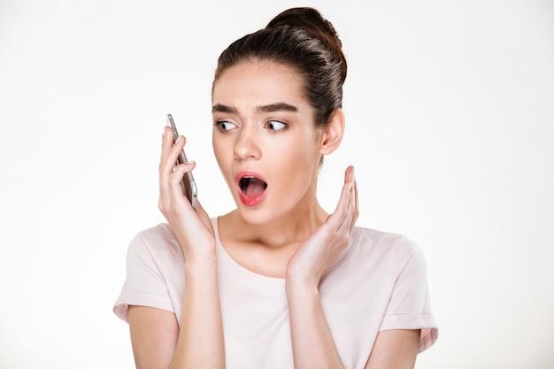 Emotionele vrouw met bruin haar in broodje die verrassing uitdrukken terwijl het hebben van mobiel gesprek