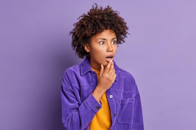 Emotionele vrouw met donkere huid laat haar kaak vallen met verbazing en verwacht niet iets angstaanjagends gekleed in een fel jasje te zien.