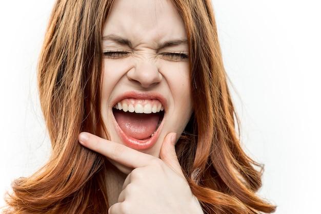 Emotionele vrouw met hand in de buurt van gezicht charme cosmetica bijgesneden weergave lichte achtergrond