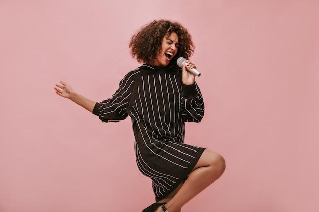 Emotionele vrouw met krullend donkerbruin haar in zwarte jurk met lange mouwen die zingt en microfoon vasthoudt op geïsoleerde muur..