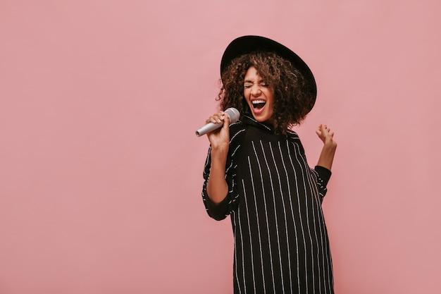 Emotionele vrouw met krullend donkerbruin kapsel in stijlvolle hoed en gestreepte zwarte jurk met microfoon en zingen op roze muur..