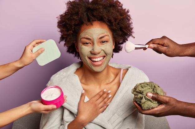 Emotionele vrouw met krullend haar lacht oprecht naar de camera, heeft een vieze huid na het nemen van een douche