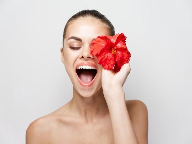 Emotionele vrouw met open mond naakte schouders rode bloem close-up