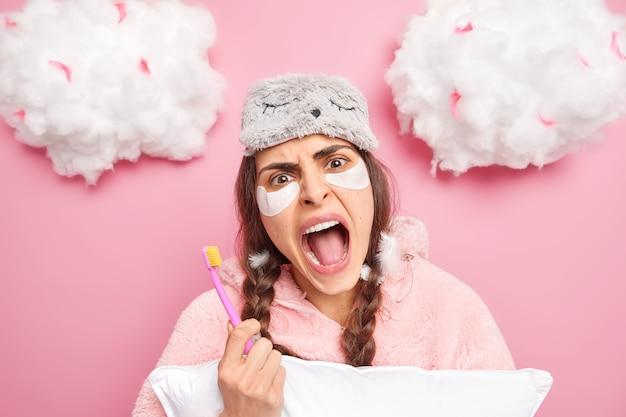 Emotionele vrouw met twee staartjes roept luide tandenborstel vast die tanden gaat poetsen na het ontwaken, gekleed in pyjama