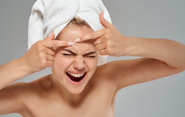 Emotionele vrouw perst puistjes op haar voorhoofd en handdoek op haar hoofd blote schouders bijgesneden weergave