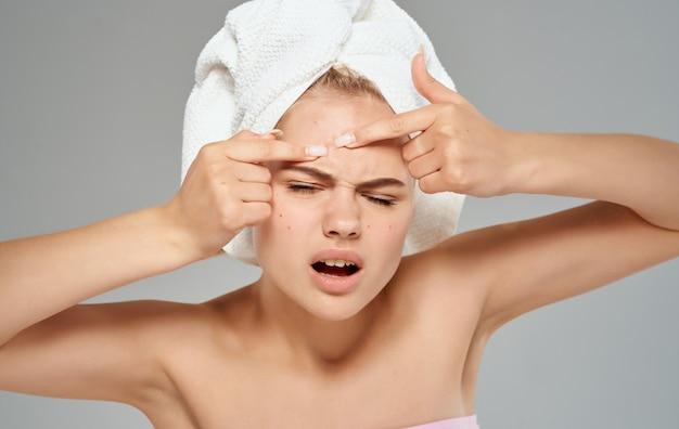 Emotionele vrouw perst puistjes op haar voorhoofd en handdoek