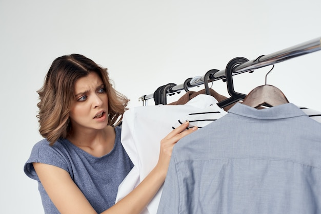 Emotionele vrouw shopaholic die kleren kiest die in de winkel geïsoleerde achtergrond winkelen
