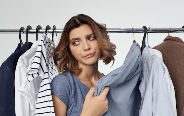 Emotionele vrouw staat in de buurt van kleren op een hanger in een kleedkamer op een lichte achtergrond winkelen. hoge kwaliteit foto