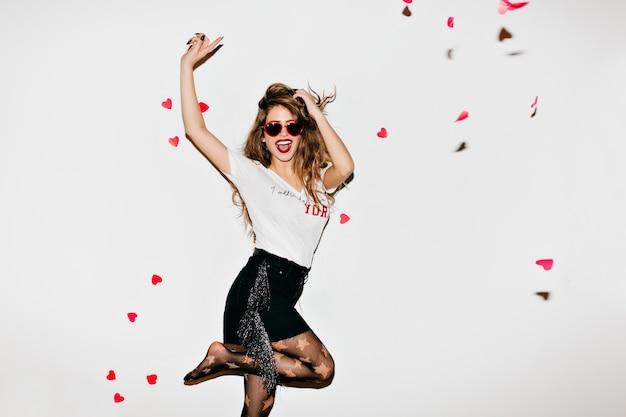 Emotionele vrouwelijke model in panty met plezier in de studio